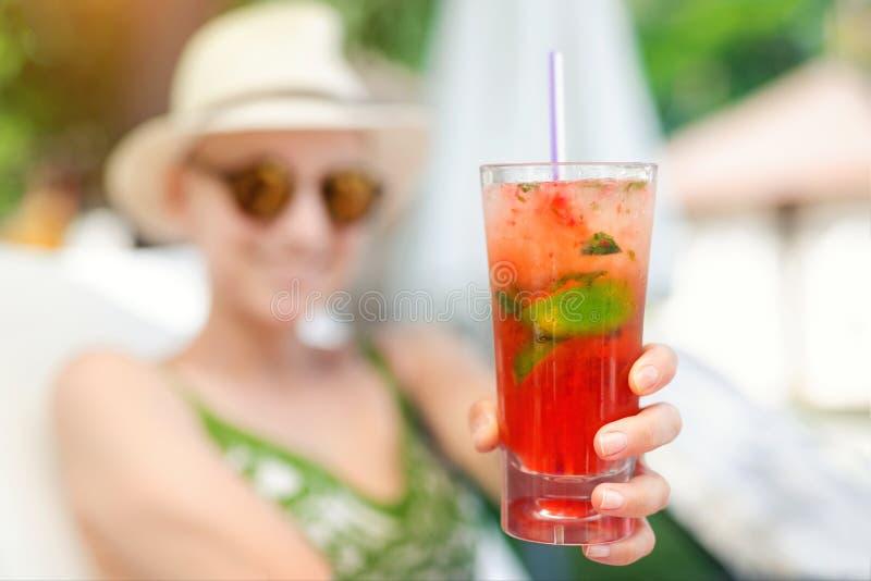 Mujer feliz hermosa joven que se sostiene a disposición y dar el vidrio con el cóctel sin alcohol del mojito de la fresa fría fre foto de archivo libre de regalías