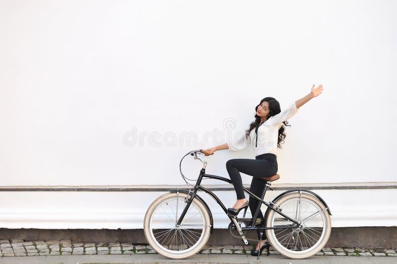 Mujer feliz hermosa que se sienta en la bicicleta y que da gestu del saludo foto de archivo libre de regalías