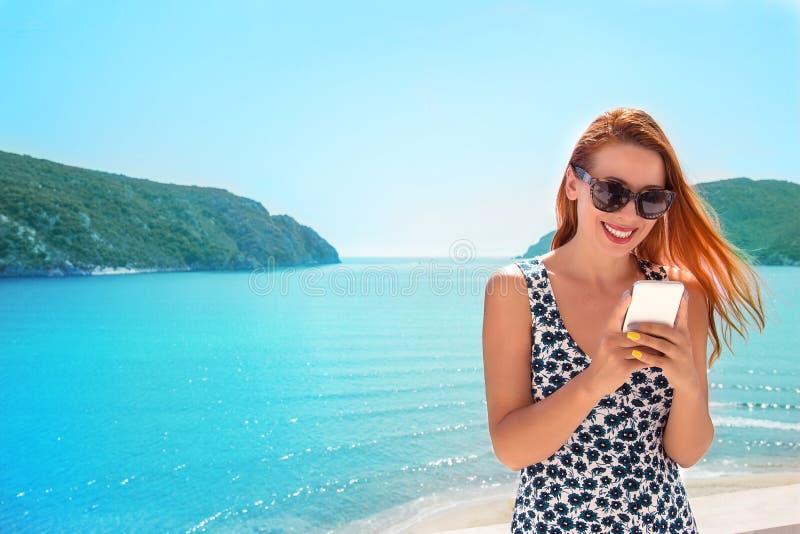 Mujer feliz hermosa que usa un teléfono elegante en un balcón de un vill fotos de archivo