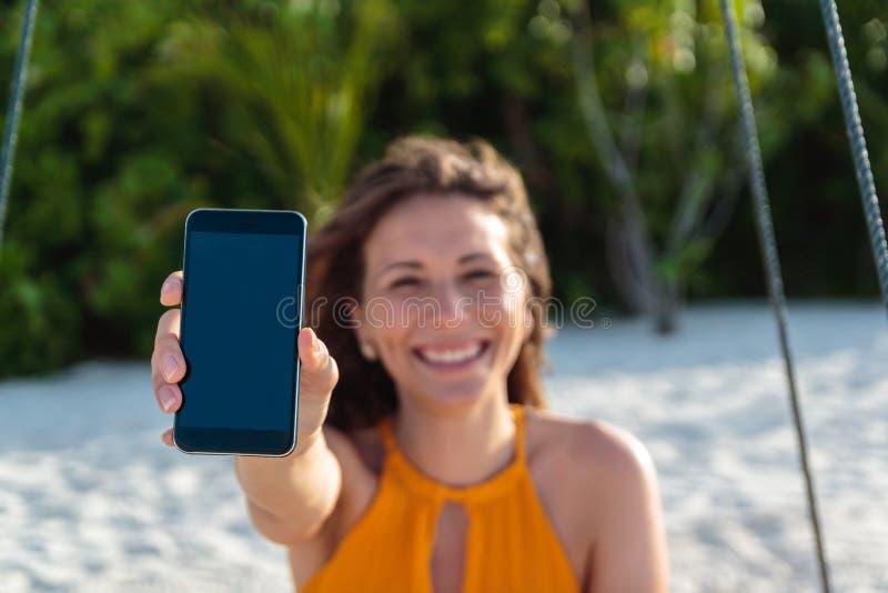 Mujer feliz joven asentada en un oscilaci?n que muestra una pantalla vertical del tel?fono Arena y selva blancas como fondo foto de archivo