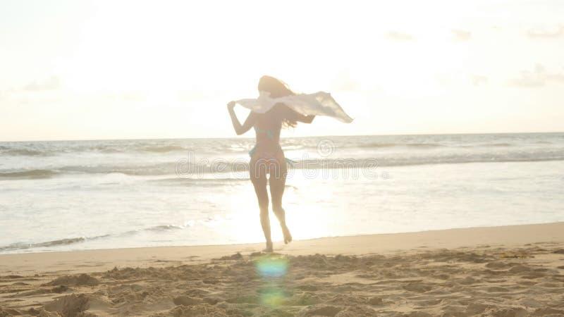 Mujer feliz joven con la bufanda que corre en la playa del océano en la puesta del sol Muchacha que disfruta de verano Hembra en  fotografía de archivo libre de regalías