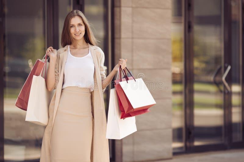 Mujer feliz joven con los panieres que camina en la calle imagenes de archivo