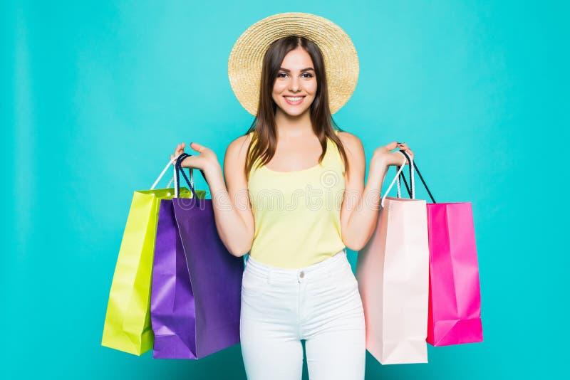 Mujer feliz joven de las compras del verano con los panieres en fondo del color imagen de archivo