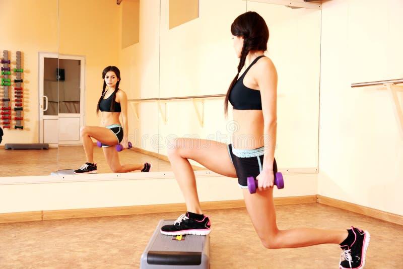 Mujer feliz joven del ajuste que hace ejercicios con los dumbells en tablero del paso imagen de archivo