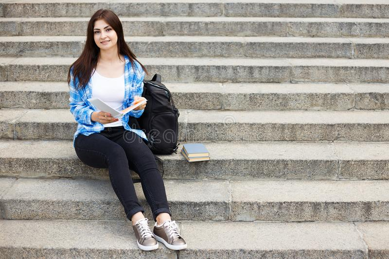 Mujer feliz joven del estudiante con los libros y la mochila que se sientan en fotos de archivo