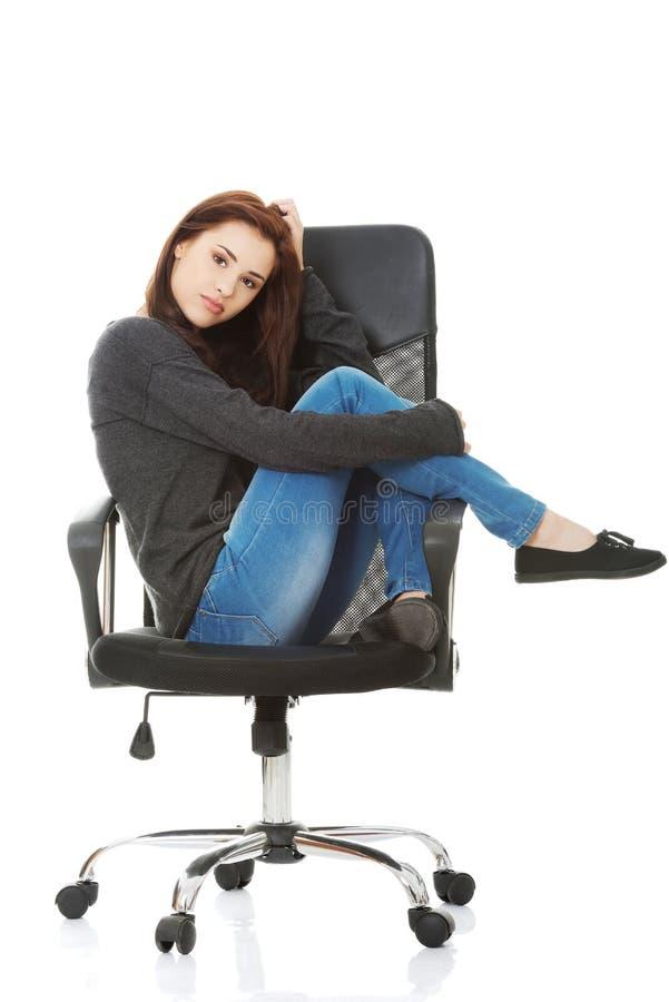 Mujer feliz joven del estudiante que se sienta en una silla de rueda imagen de archivo