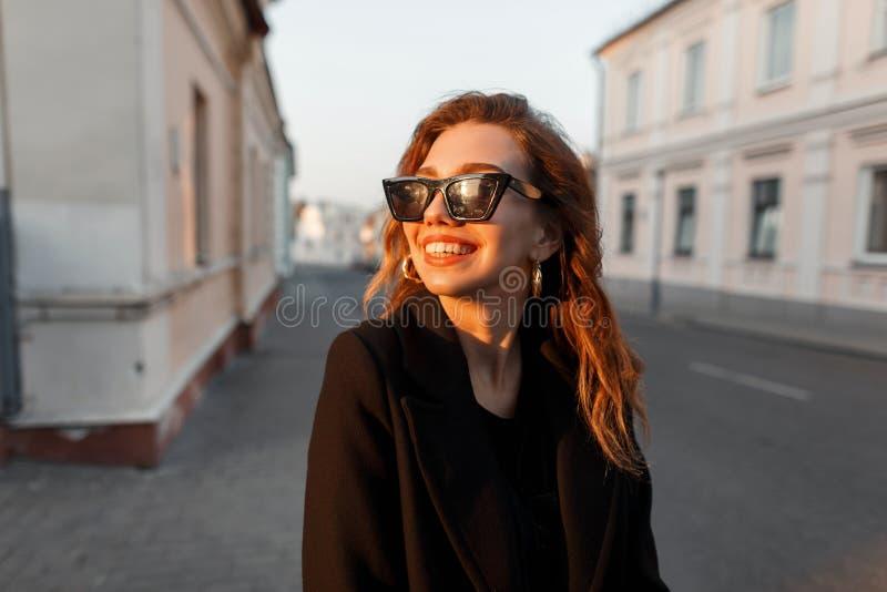 Mujer feliz joven del inconformista con una sonrisa positiva en lentes de sol negros en una capa elegante que presenta cerca de u fotos de archivo libres de regalías