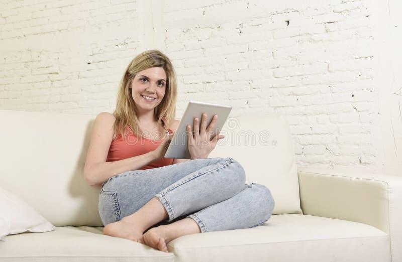 Mujer feliz joven en el sofá casero usando Internet app en el cojín digital de la tableta imagen de archivo libre de regalías