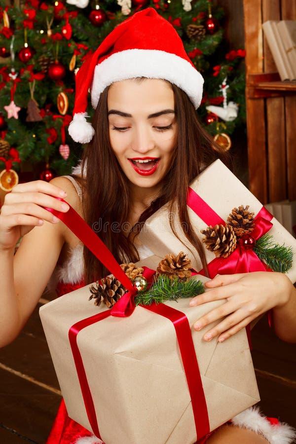 Mujer feliz joven en el sombrero rojo de santa y el vestido rojo cerca del Año Nuevo t fotografía de archivo libre de regalías