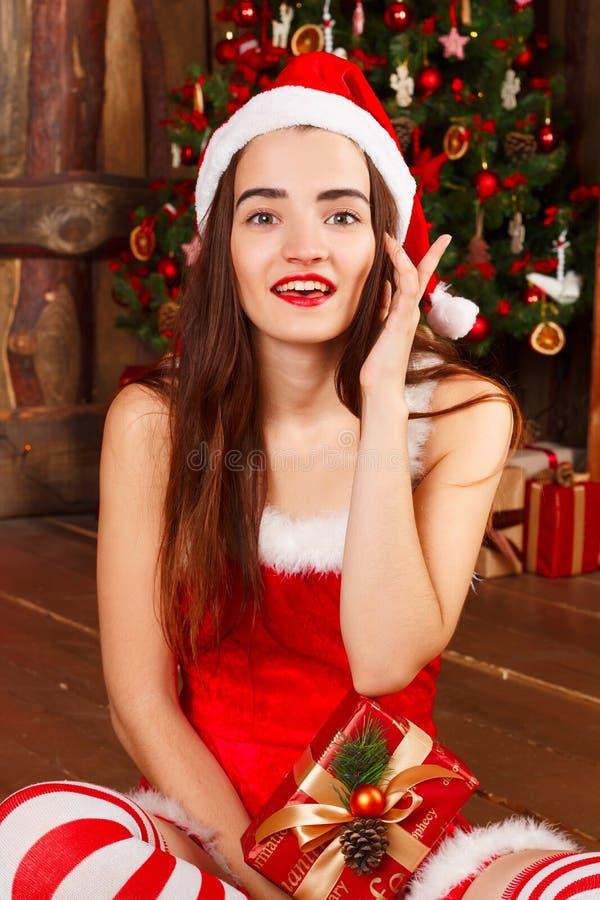 Mujer feliz joven en el sombrero rojo de santa y el vestido rojo que se sientan cerca del ne foto de archivo