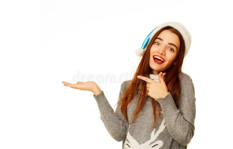 Mujer feliz joven en el sweather caliente que sostiene su producto sobre wh foto de archivo
