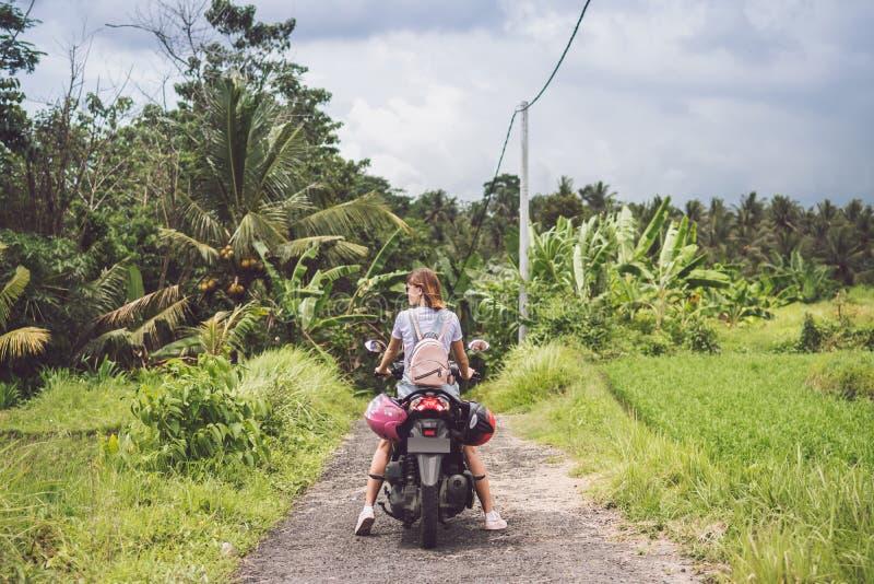 Mujer feliz joven en una moto en la selva tropical de la selva de una isla tropical de Bali, Indonesia Concepto de la libertad Se imagen de archivo libre de regalías
