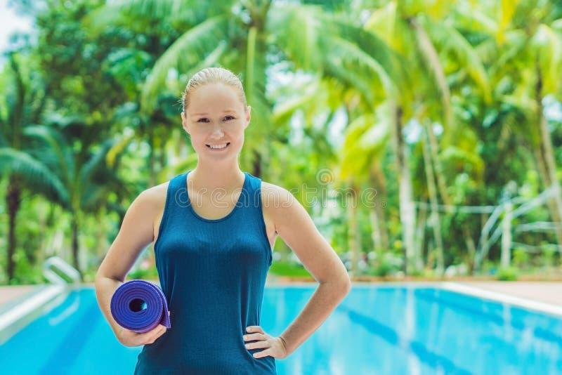Mujer feliz joven hermosa que hace ejercicio de la yoga cerca de piscina Forma de vida sana y buenos conceptos de la salud imágenes de archivo libres de regalías