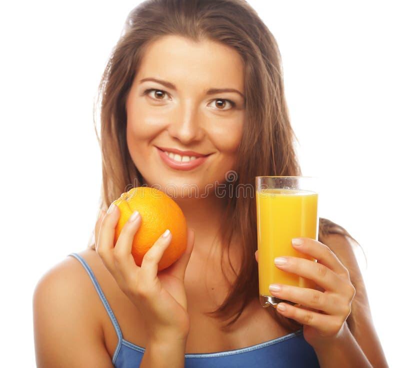 Mujer feliz joven que bebe el zumo de naranja foto de archivo libre de regalías