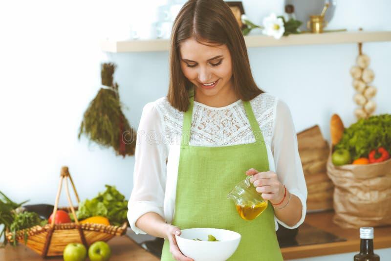 Mujer feliz joven que cocina en la cocina Comida sana, forma de vida y conceptos culinarios La buena ma?ana comienza con fresco imagen de archivo libre de regalías