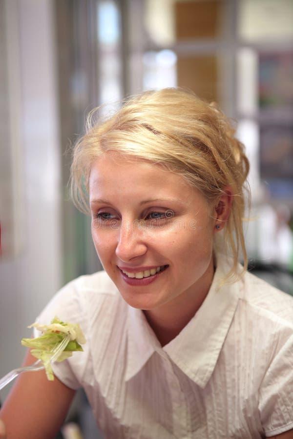Mujer feliz joven que come la ensalada foto de archivo