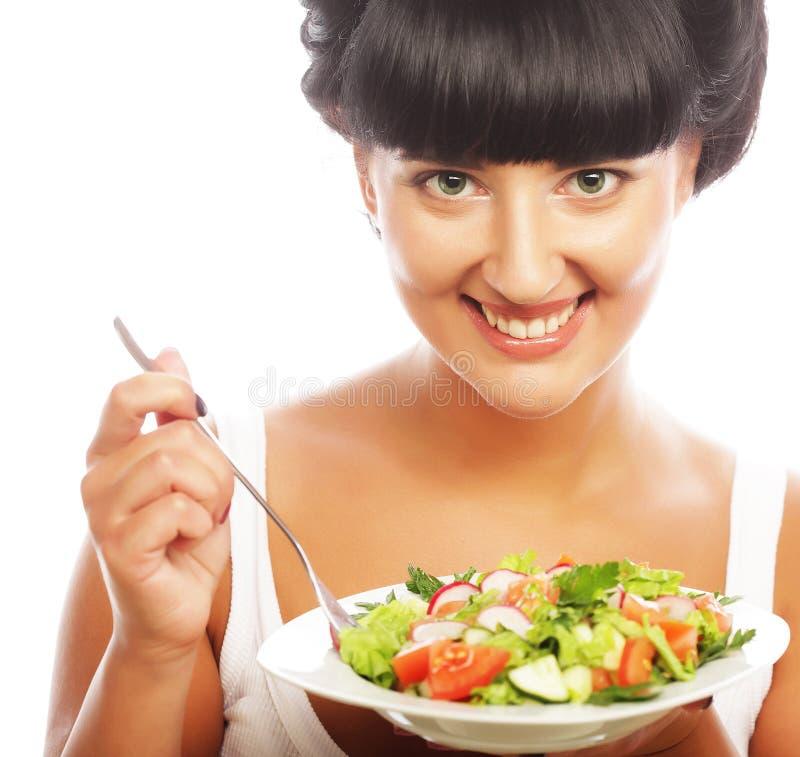 Mujer feliz joven que come la ensalada fotografía de archivo