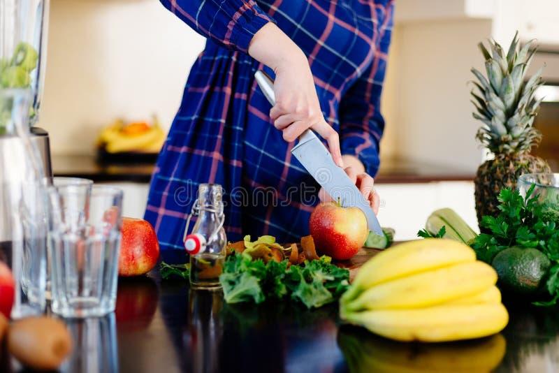Mujer feliz joven que corta la manzana para el smoothie foto de archivo
