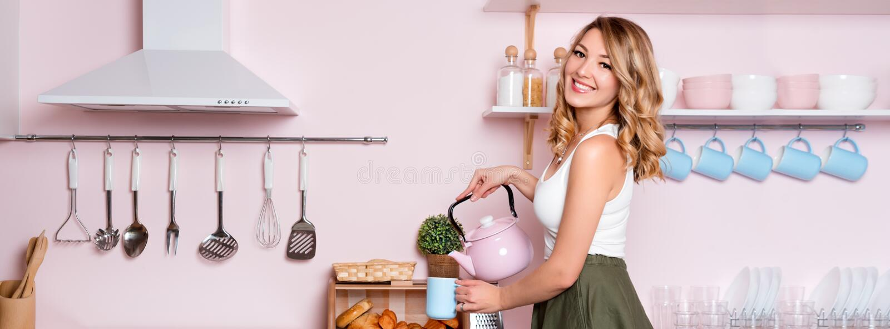 Mujer feliz joven que hace el café o el té en casa en la cocina Muchacha hermosa rubia que desayuna su antes de ir foto de archivo libre de regalías