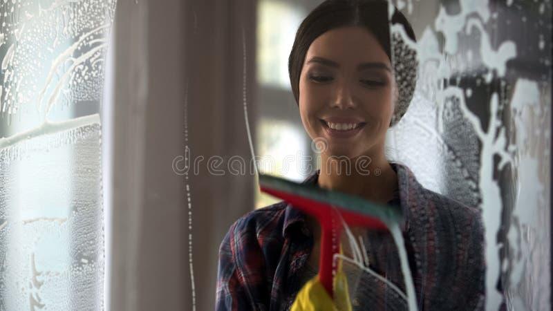 Mujer feliz joven que limpia la superficie de cristal después del espray, calidad de limpieza del servicio fotografía de archivo