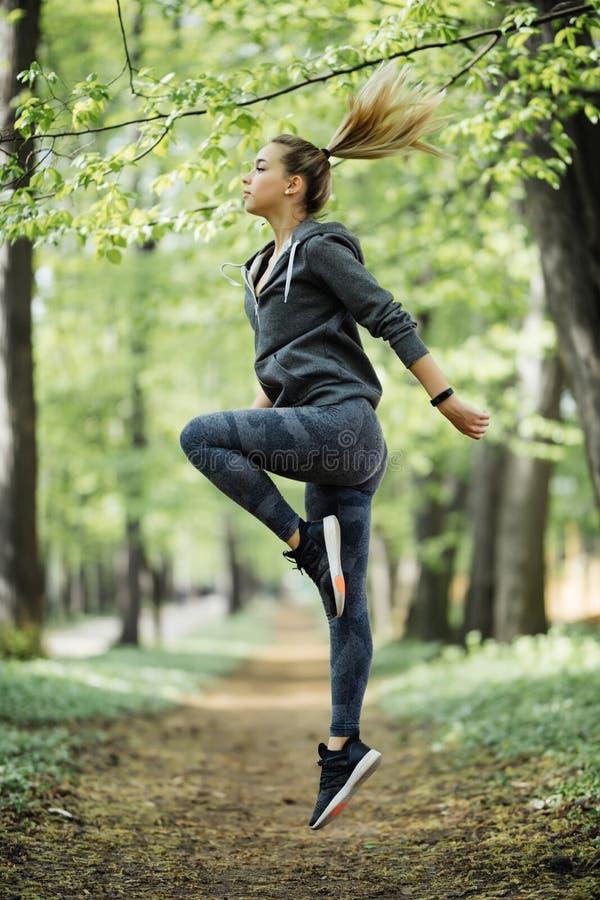 Mujer feliz joven que salta en parque Entrenamiento femenino del modelo de la aptitud afuera en un día caliente de la caída Forma fotografía de archivo