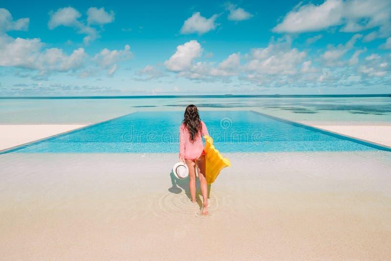 Mujer feliz joven que se relaja en una piscina fotografía de archivo libre de regalías