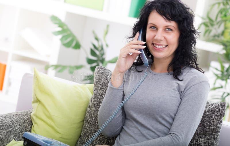 Mujer feliz joven que se sienta en el sofá en casa mientras que habla en p fotos de archivo libres de regalías