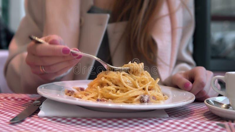Mujer feliz joven que se sienta en la tabla en café y que disfruta de la comida Mujer hambrienta que come las pastas sabrosas fotos de archivo