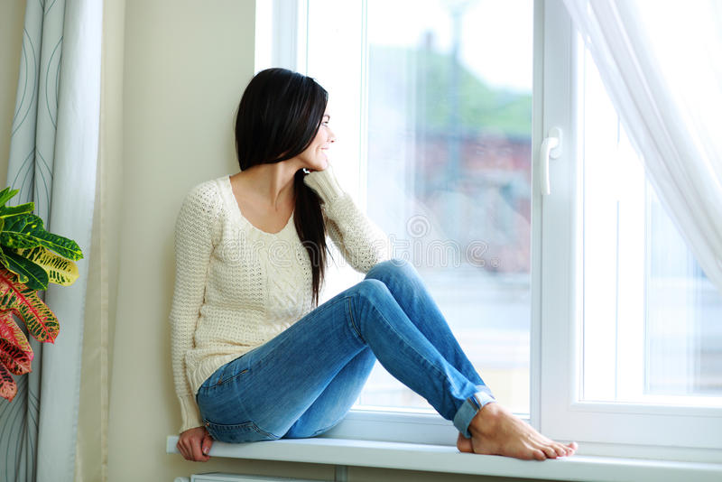 Mujer feliz joven que se sienta en un ventana-travesaño imagenes de archivo