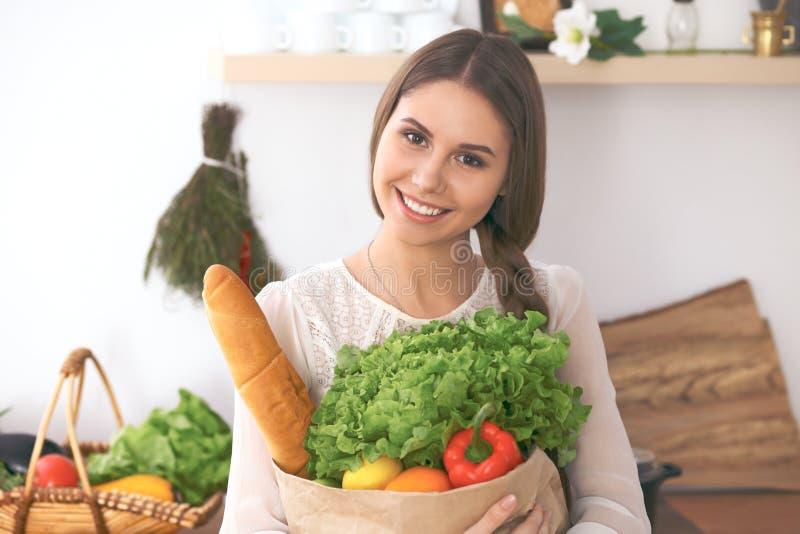 Mujer feliz joven que sostiene la bolsa de papel llena de verduras y de frutas mientras que sonríe La muchacha ha hecho compras y fotos de archivo libres de regalías