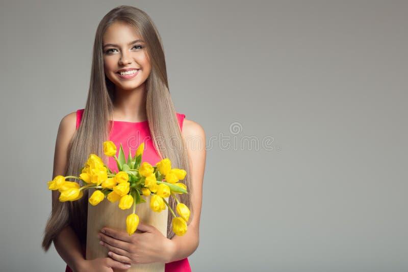 Mujer feliz joven que sostiene la cesta con los tulipanes amarillos imagenes de archivo