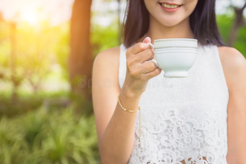 Mujer feliz joven que sostiene la taza o el té de café por mañana imagen de archivo libre de regalías