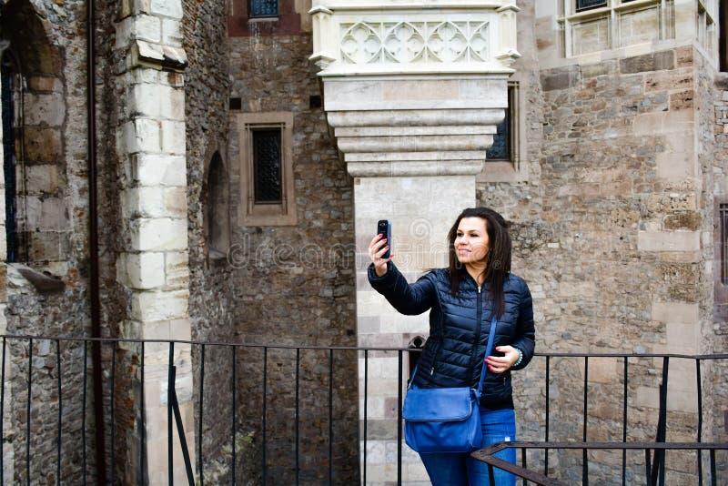 Mujer feliz joven que toma un selfie en el castillo de Corvin, Rumania fotos de archivo libres de regalías