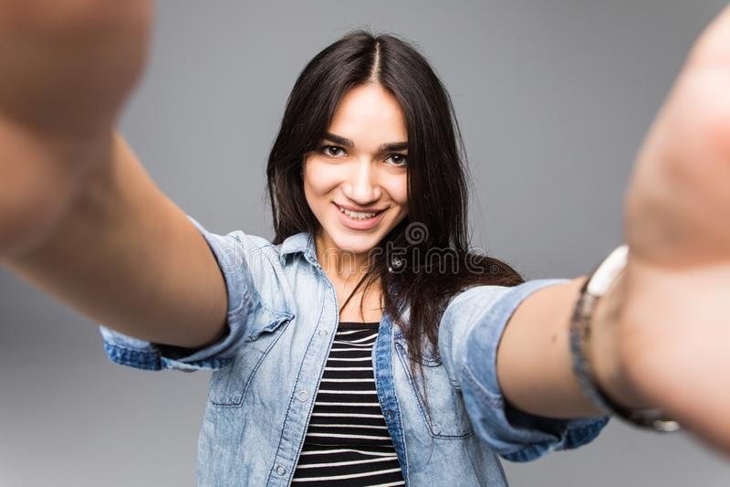 Mujer feliz joven que toma un selfie en un fondo gris fotografía de archivo