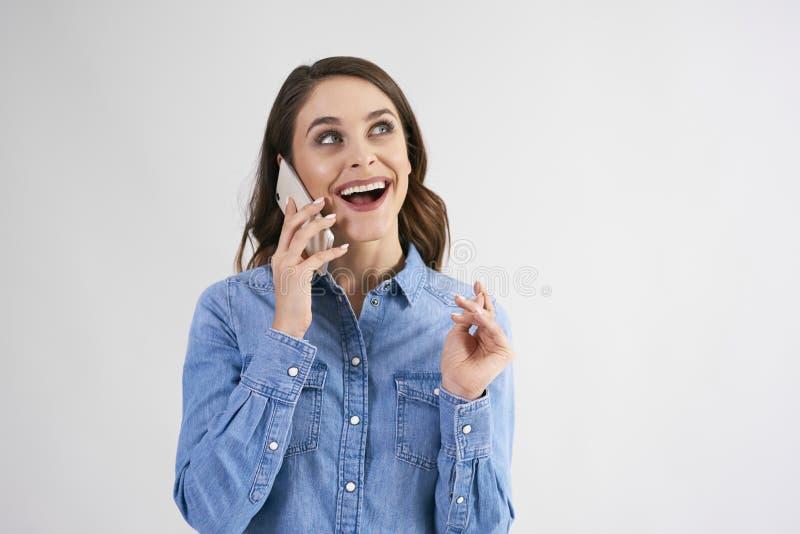 Mujer feliz, joven usando el teléfono móvil en tiro del estudio foto de archivo