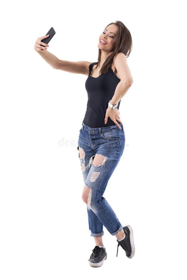 Mujer feliz latina magnífica de la belleza que toma las fotos del selfie con el teléfono móvil Vista lateral imágenes de archivo libres de regalías
