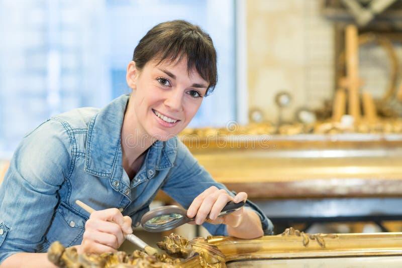 Mujer feliz limpiando la dorada del marco antiguo imagenes de archivo