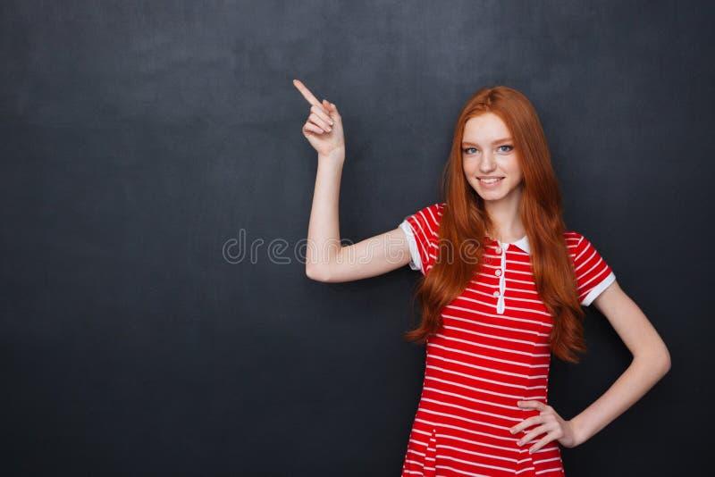 Mujer feliz linda que señala en copyspace sobre fondo de la pizarra foto de archivo libre de regalías