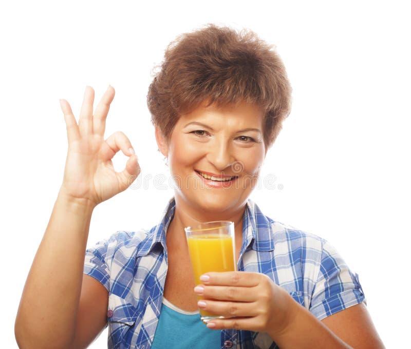 Mujer feliz madura con el zumo de naranja imágenes de archivo libres de regalías