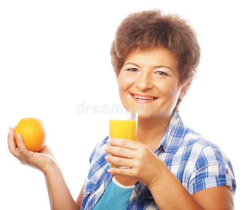 Mujer feliz madura con el zumo de naranja fotos de archivo