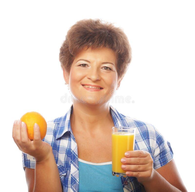 Mujer feliz madura con el zumo de naranja foto de archivo libre de regalías