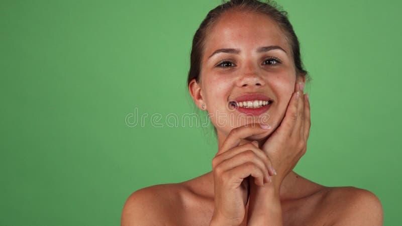 Mujer feliz magnífica que toca su cara que sonríe suavemente a la cámara imagen de archivo