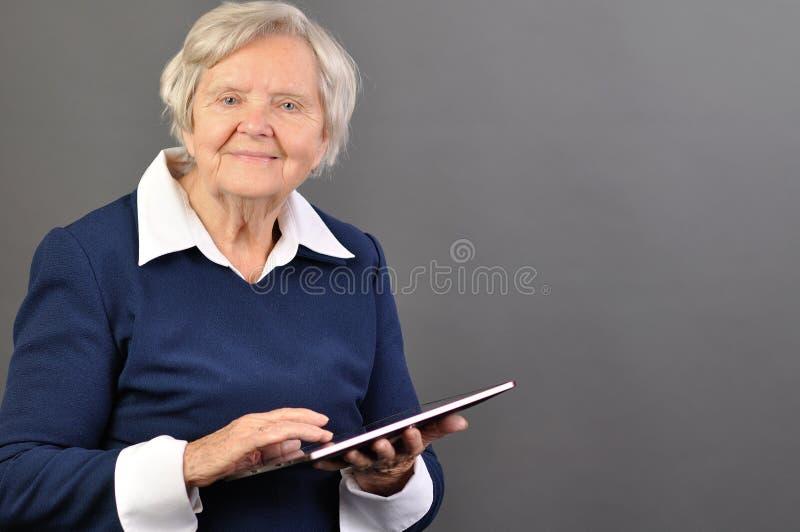 Mujer feliz mayor con la tablilla. imagenes de archivo