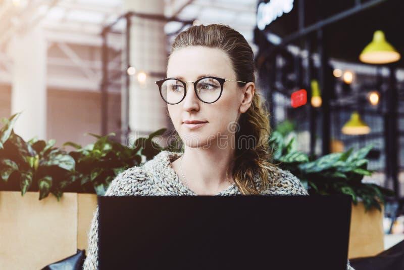 Mujer feliz milenaria usando el ordenador port?til mientras que se sienta en el caf? Empresaria joven que se sienta en la cafeter fotografía de archivo