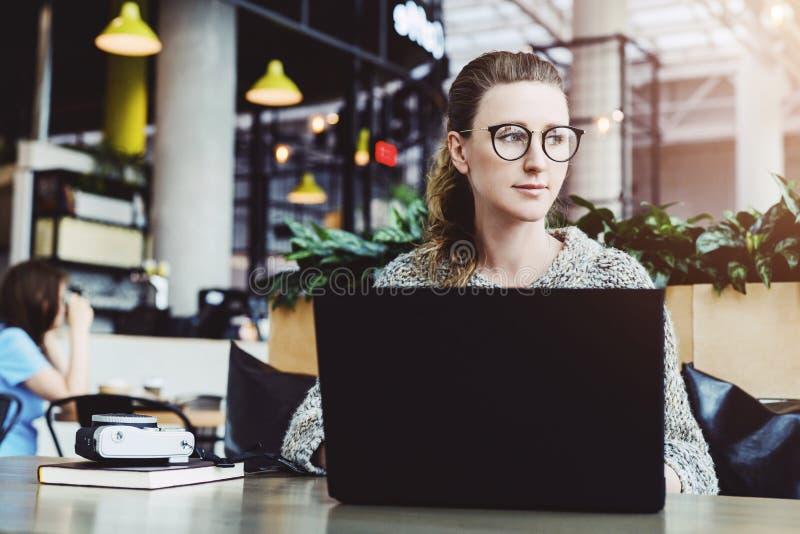 Mujer feliz milenaria usando el ordenador port?til mientras que se sienta en el caf? Empresaria joven que se sienta en la cafeter fotos de archivo