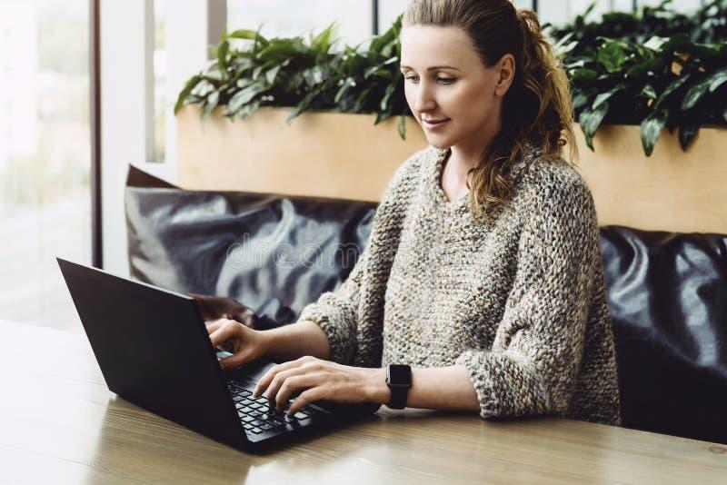 Mujer feliz milenaria usando el ordenador port?til mientras que se sienta en el caf? Empresaria joven que se sienta en la cafeter fotos de archivo libres de regalías