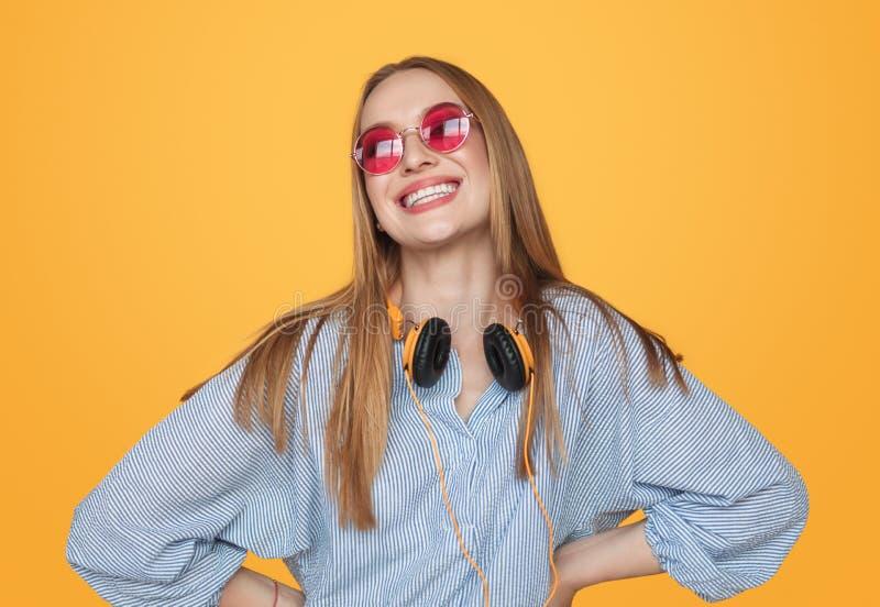 Mujer feliz moderna del inconformista con los auriculares imagen de archivo