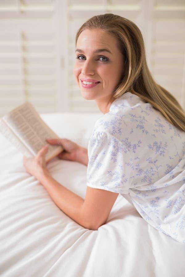 Mujer feliz natural que miente en la cama que sostiene el libro imágenes de archivo libres de regalías