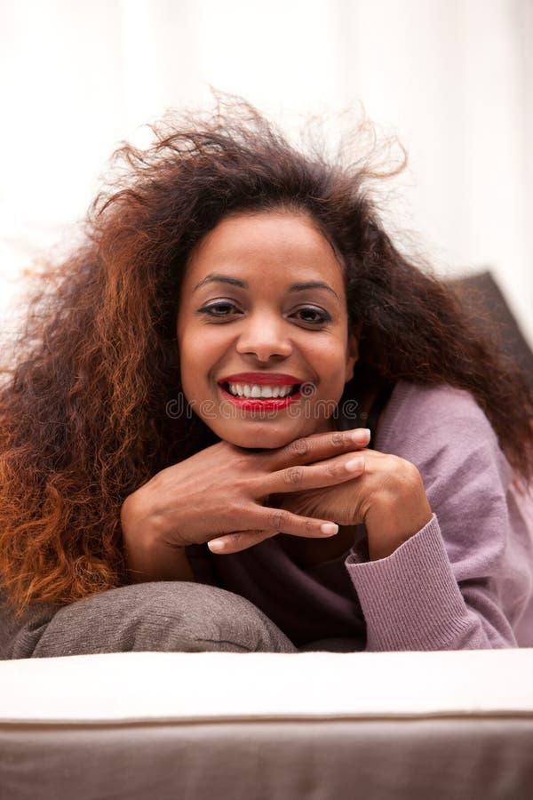 Mujer feliz negra joven hermosa en un sofá imagenes de archivo