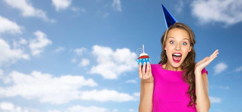 Mujer feliz o muchacha adolescente con la magdalena del cumpleaños fotografía de archivo